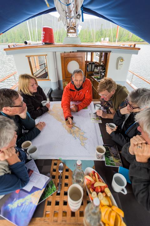 Captain Russel Markel charts the day's sailing plan with guets