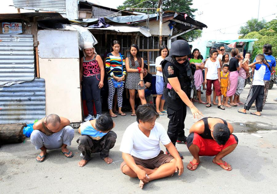 Police detain residents for questioning in Manila.